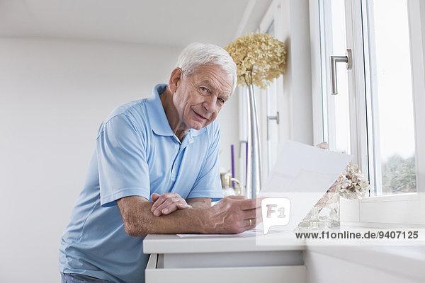 Senior Senioren Mann Papier halten Tuch