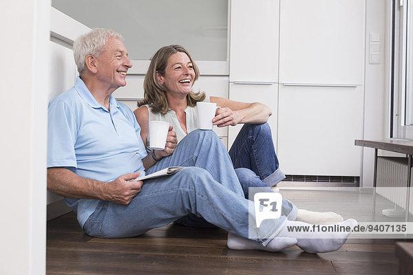 sitzend Fröhlichkeit Boden Fußboden Fußböden trinken Kaffee