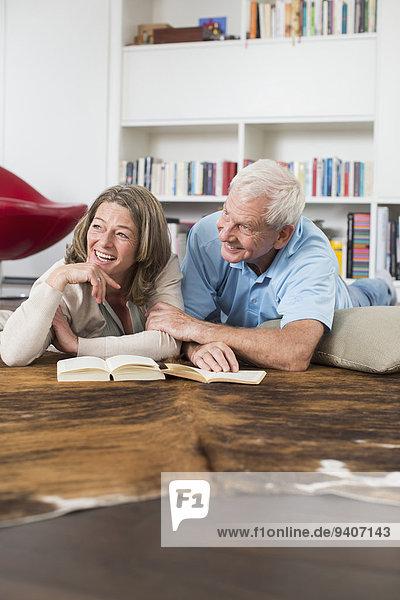 Happy couple lying on floor reading book