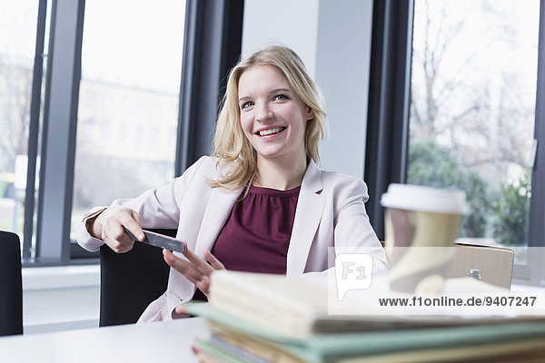 Businesswoman filing her nails in office