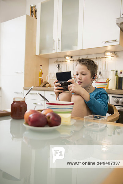Boy playing video game in kitchen
