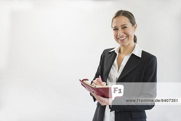Stift Stifte Schreibstift Schreibstifte Portrait Geschäftsfrau lächeln halten schwarz Notizblock Notebook