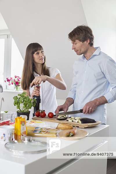 Mid adult woman opening wine bottle while mature man cutting vegetable