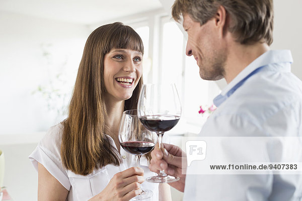 Couple having glass of wine together,  smiling