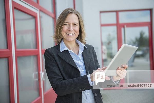 Portrait of businesswoman using digital tablet  smiling