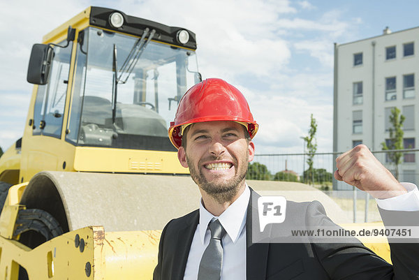 Businessman with hard hat cheering on construction site
