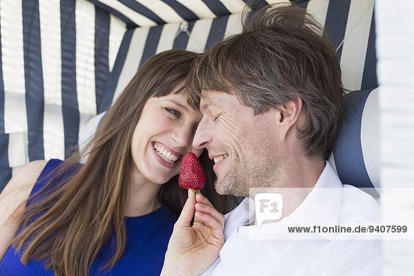 Stuhl lächeln Strand Erdbeere Dach essen essend isst Peddigrohr