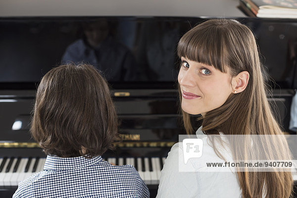 Mother and daughter playing piano  close up
