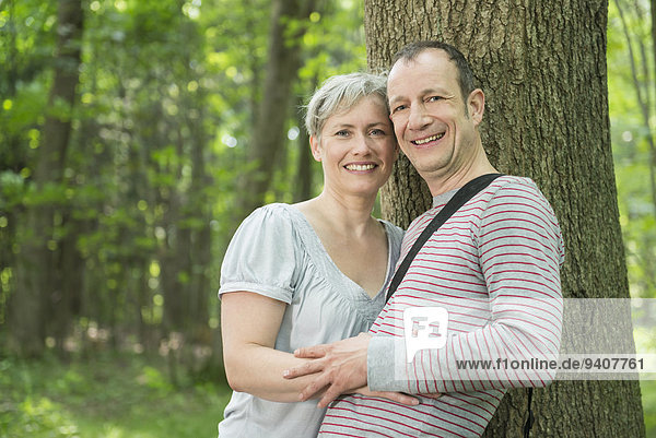 Portrait of mature couple leaning by tree in forest  smiling