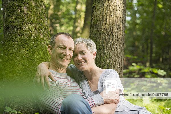 sitzend Portrait lächeln Baum Wald reifer Erwachsene reife Erwachsene