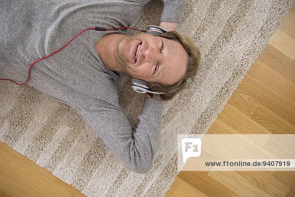 liegend, liegen, liegt, liegendes, liegender, liegende, daliegen, Mann, zuhören, Entspannung, Musik, Teppichboden, Teppich, Teppiche, Klassisches Konzert, Klassik