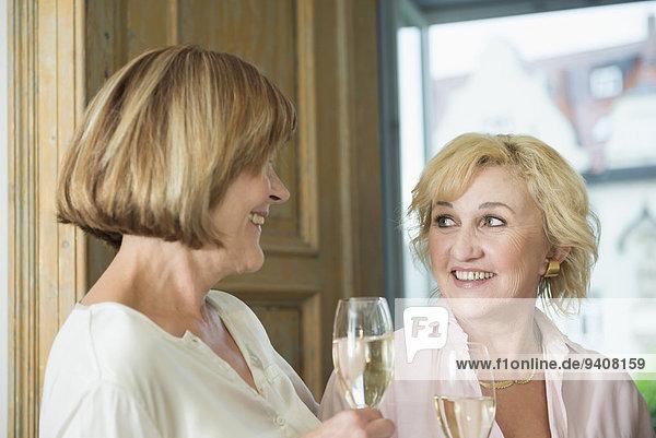 Frau Glas lächeln Wein halten glitzern Gespräch Gespräche Unterhaltung Unterhaltungen