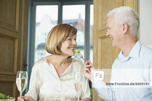 Man feeding to woman,  smiling