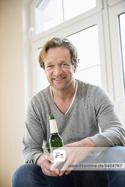 Mann lächeln halten Bier Flasche