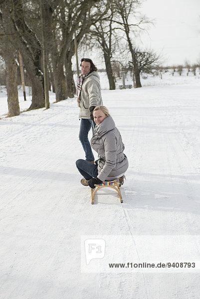 Frau Mann ziehen Schlitten Schnee