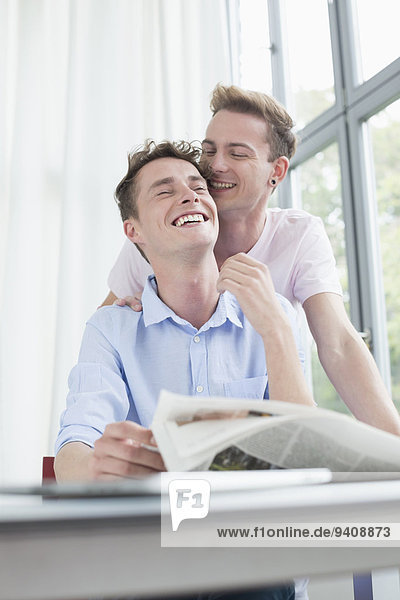 Homosexual couple cuddling each other while reading newspaper  smiling