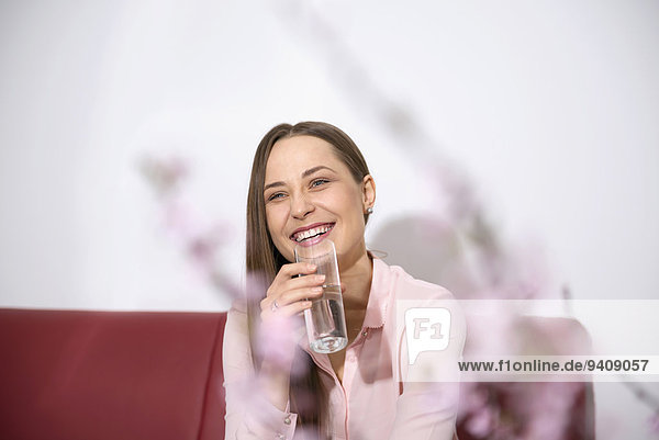 Young woman sofa sitting smiling drinking water