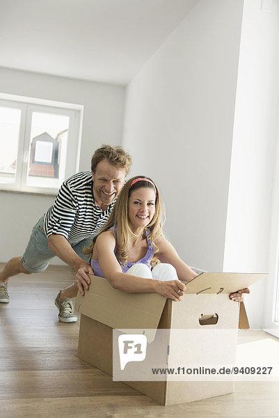 Frau Mann schieben innerhalb Eigentumswohnung neues Zuhause