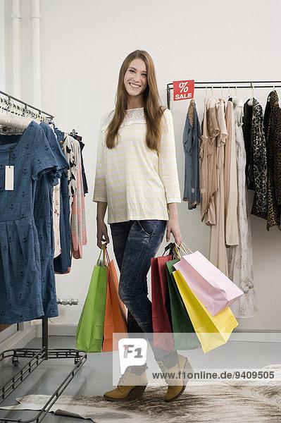 junge Frau junge Frauen Portrait lächeln Tasche halten kaufen