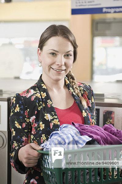 junge Frau junge Frauen Portrait lächeln Korb halten Wäsche