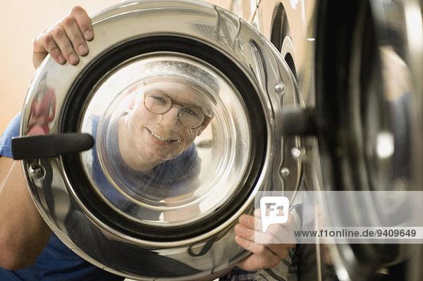 Mann sehen Fenster lächeln waschen Maschine blättern jung