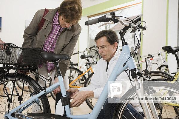 zeigen Verkäufer Frau Fahrrad Rad