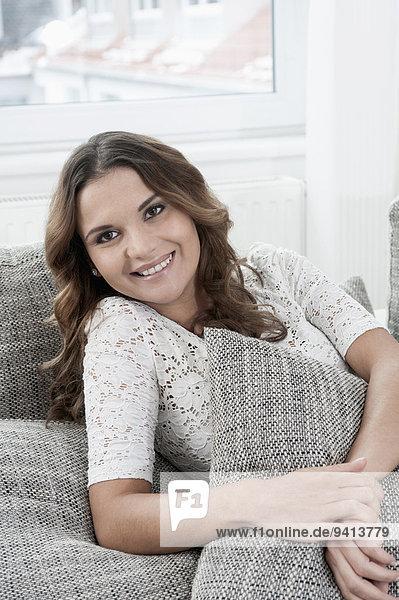 sitzend Interior zu Hause junge Frau junge Frauen Portrait lächeln Couch