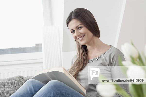 sitzend Interior zu Hause junge Frau junge Frauen Portrait Buch lächeln offen Couch Taschenbuch