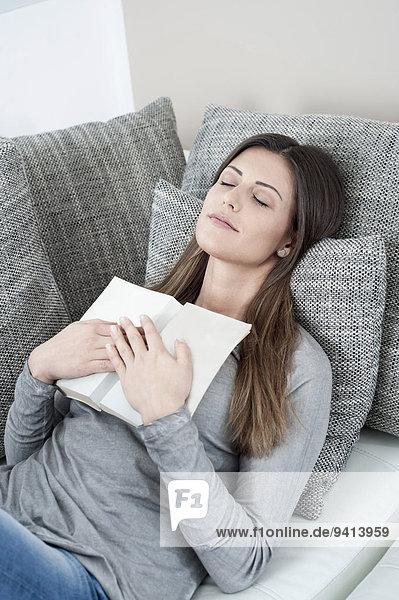 Interior, zu Hause, junge Frau, junge Frauen, Portrait, Buch, offen, schlafen, Couch, Taschenbuch