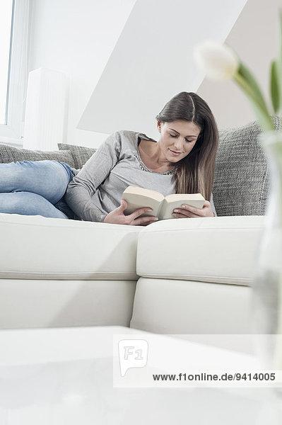 Interior zu Hause junge Frau junge Frauen Buch Couch Taschenbuch vorlesen