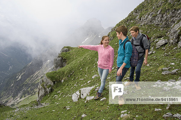 Girl and teenage boys hiking in mountains