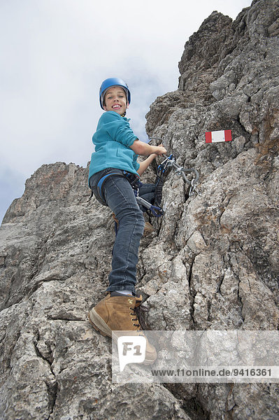 Young teenage boy holding rope on rock face