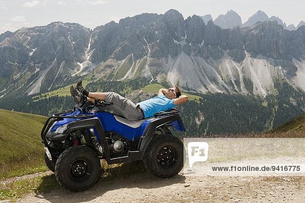 Man sunbathing on Quad bike in mountain landscape