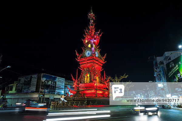 Colourfully illuminated Clock Tower at night with light trails of vehicles  Wiang Mueang  Chiang Rai Province  Chiang Rai Province  Northern Thailand  Thailand