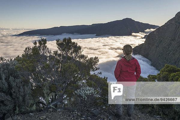 Junge Frau schaut über Wolkenmeer über Talkessel Cilaos  Cirque de Cilaos  La Reunion