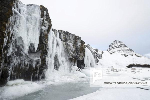 Berg Kirkjufell hinter gefrorenem Wasserfall Kirkjufellsfoss im Schnee  Snaefellsnes Halbinsel  Island
