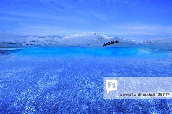 Monte Vettore zur blauen Stunde mit einer gefrorenen Pfütze mit Luftblasen  Nationalpark Monti Sibillini  Umbrien  Italien