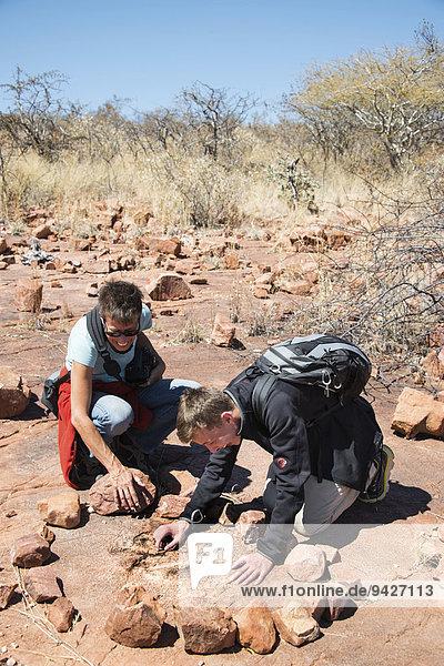 Zwei Touristen schauen nach versteinerten Dinosaurier Fußabdrücken  Kalkfeld  Otjozondjupa  Namibia