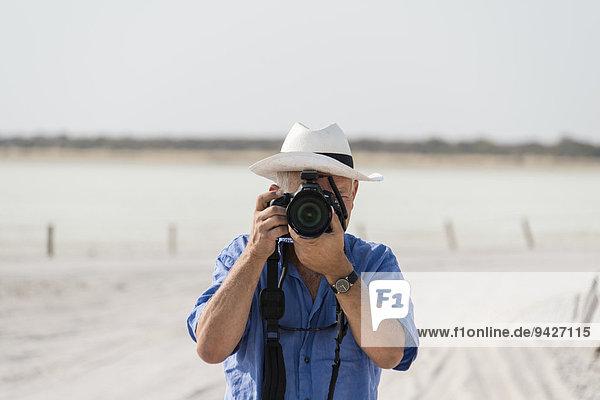 Mann fotografiert  Etosha-Pfanne  Salzpfanne  Etosha-Nationalpark  Namibia