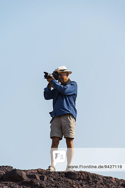Mann fotografiert auf einem Felsen stehend  Namibia