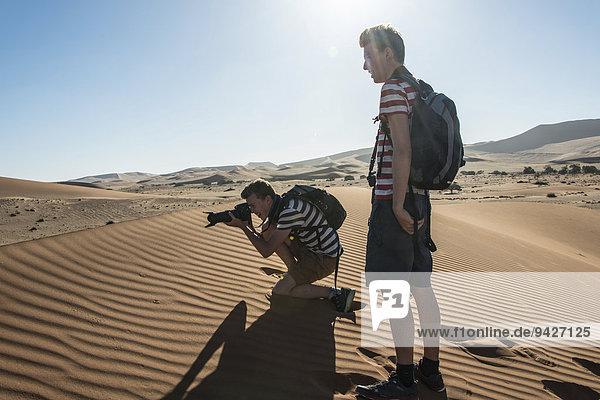 Zwei Jugendliche stehen auf einer Düne  einer fotografiert  Sossusvlei  Namib-Wüste  Hardap  Namibia