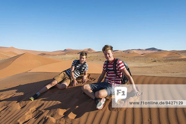 Zwei Jugendliche sitzen erschöpft auf einer Düne  Sossusvlei  Namib-Wüste  Namibia
