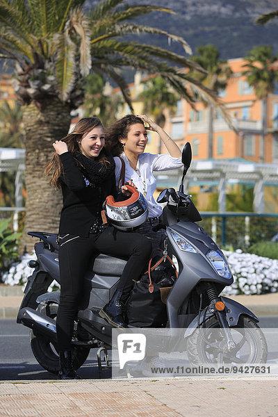 Zwei Freundinnen  Teenager  mit einem Motorroller  Menton  Alpes-Maritimes  Provence-Alpes-Côte d'Azur  Frankreich