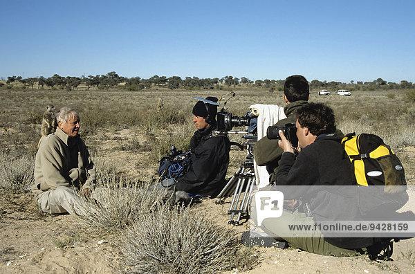 Sir David Attenborough mit Erdmännchen auf der Schulter  Filmarbeiten für BBC-Serie Life of Mammals  Produzent Huw Cordey vorne rechts  Kalahari  Provinz Nordkap  Südafrika
