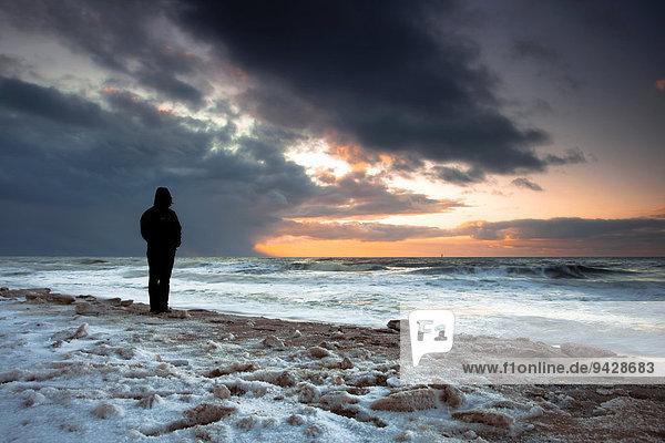 Frau schaut auf die Nordsee mit Sonnenuntergang an einem Wintertag auf der Insel Sylt  Schleswig-Holstein  Deutschland  Europa