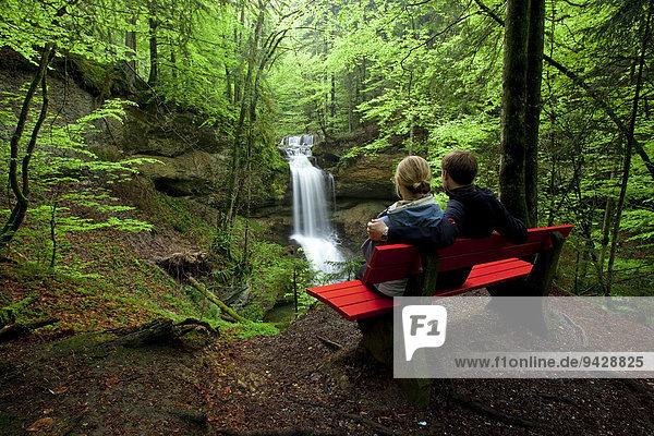 Paar auf Sitzbank am Hasenreuter Wasserfall mit Scheidegg  Allgäu  Deutschland  Europa