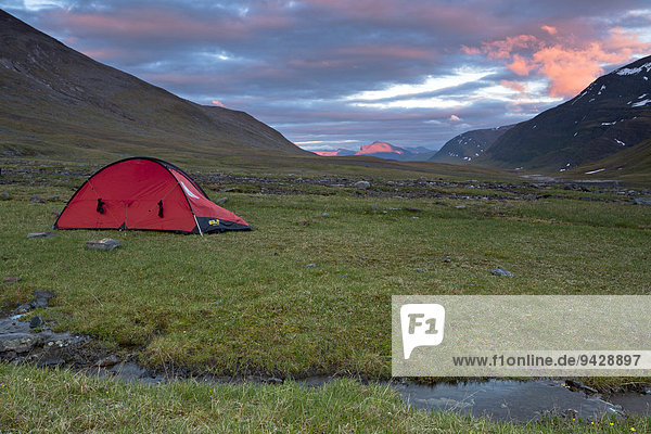 Midnight sun in the Fjaell Mountains with a small stream and a red tent  Kungsleden  The King's Trail  Lapland  Sweden  Europe