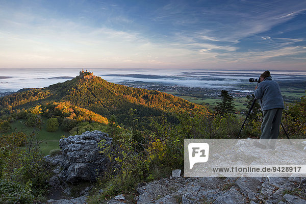 Die Burg Hohenzollern mit Fotograf im morgendlichen Herbstlicht mit Herbstwald  Frühnebel. Schwäbische Alb  Deutschland  Europa