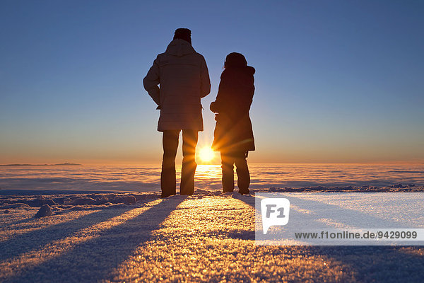Two people standing in front of sunset on Schauinsland Mountain in the Black Forest  Baden-Wuerttemberg  Germany  Europe