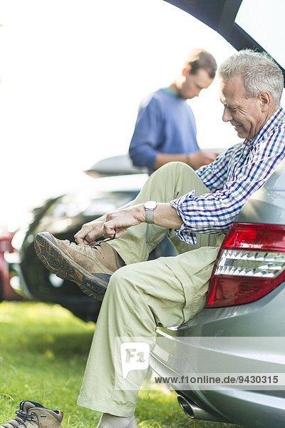Man sitting on car boot tying shoelaces